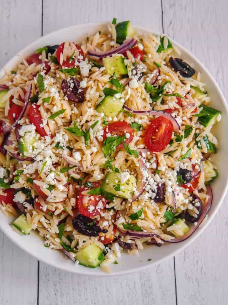 overhead shot of white bowl with orzo pasta, cucumbers, tomatoes, cucumbers, red onions, feta cheese over the top