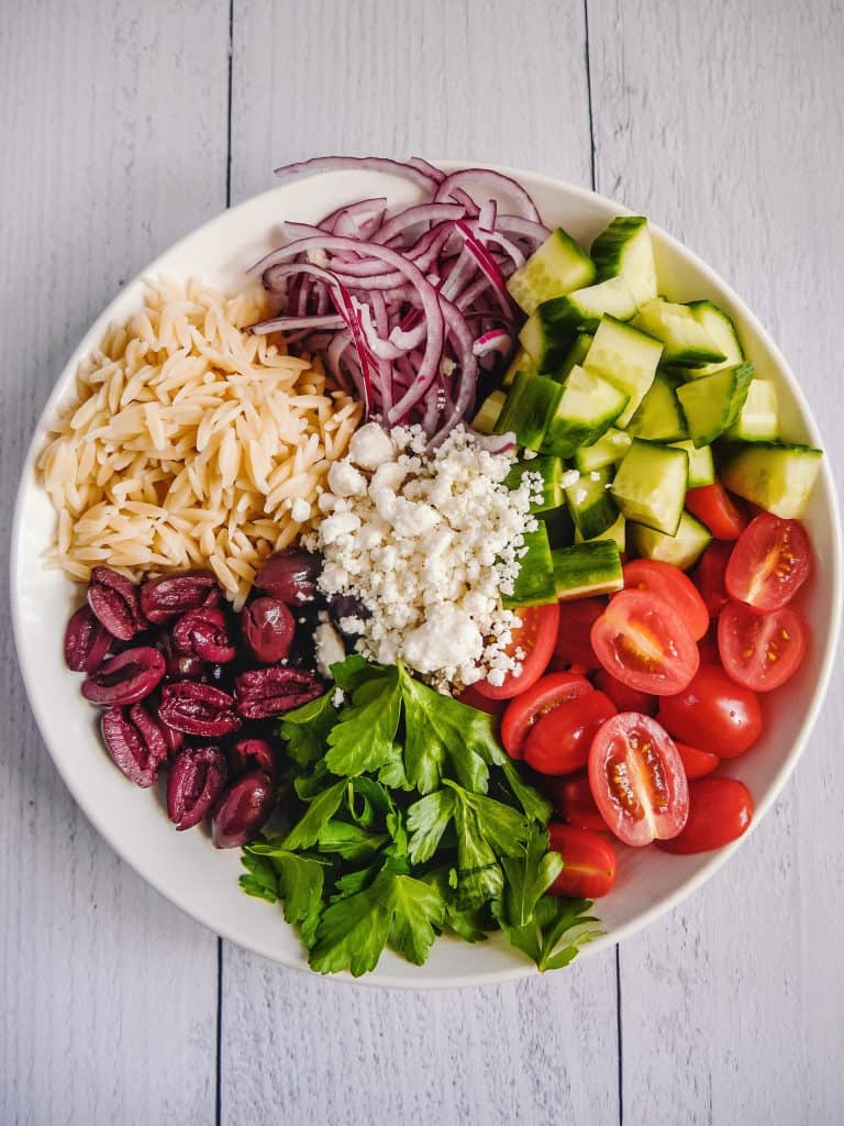 overhead shot of white bowl with orzo pasta, cucumbers, tomatoes, cucumbers, red onions, feta cheese all separated