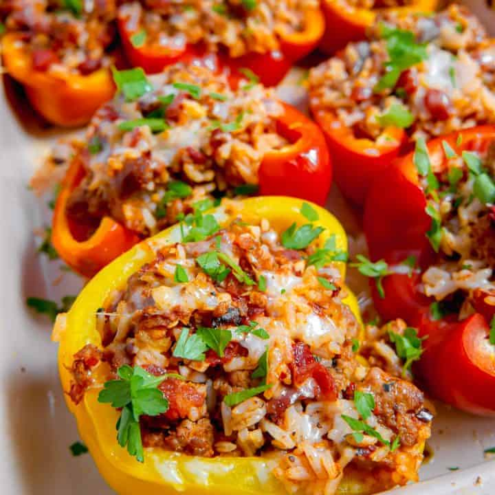 close up photo of stuffed yellow pepper in a baking dish filled with sausage and rice