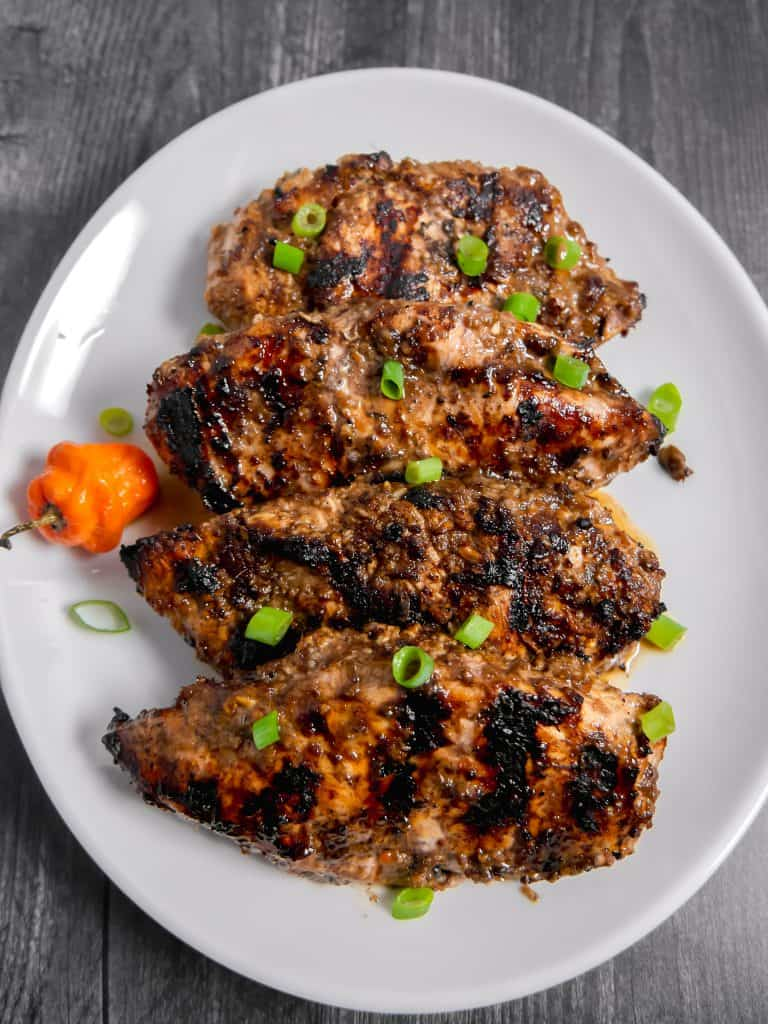 Grilled jerk chicken on plate with scotch bonnet pepper