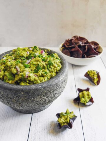 guacamole in a stone bowl with chips