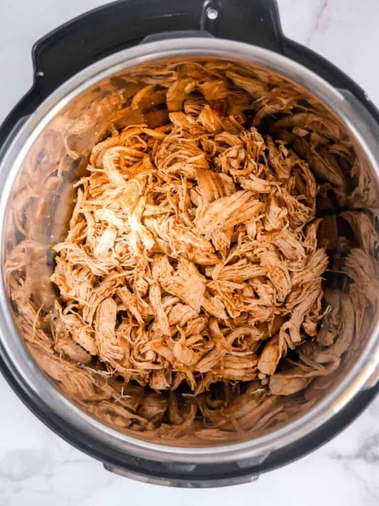overhead shot of cooked shredded chicken inside of the instant pot pressure cooker