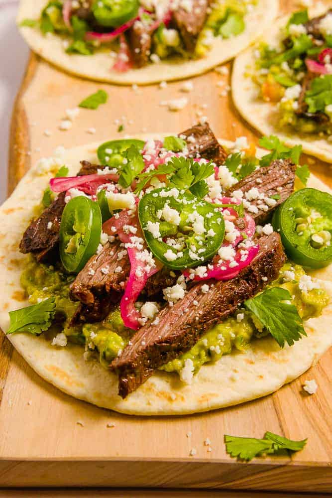 close up of a tortilla on a wood plant with guac, pickled red onions, carne asada, jalapenos