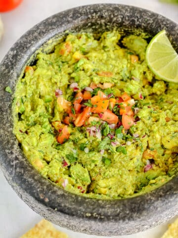 guacamole in a molcajete surrounded by chips