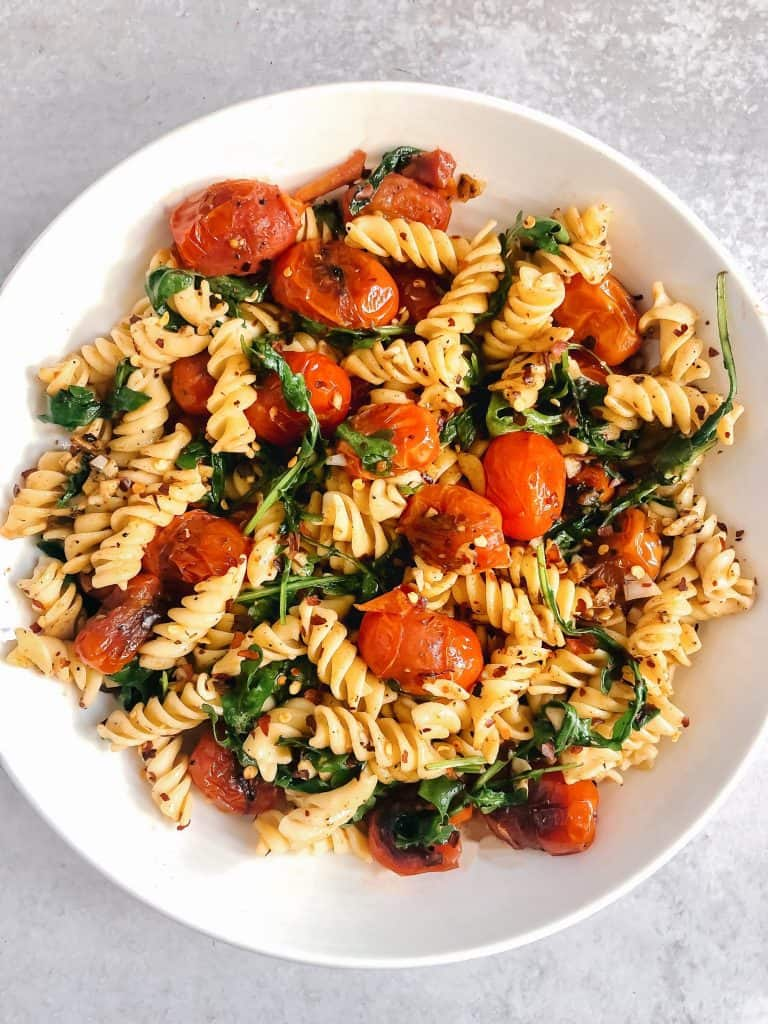 Blistered tomato pasta with fresh arugula, garlic, and gluten free pasta