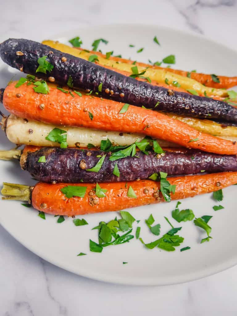 side shot of roasted rainbow carrots with coriander seeds and chopped parsley stacked up on a white plate