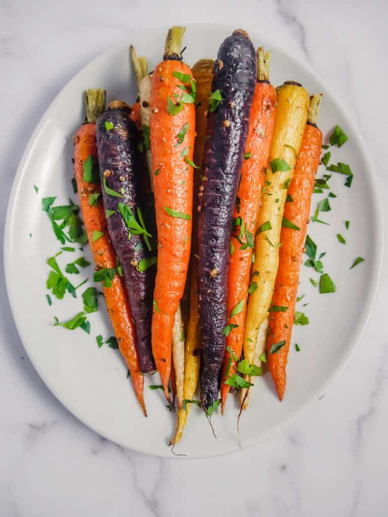 overhead shot of roasted rainbow carrots with chopped parsley stacked up on a white plate