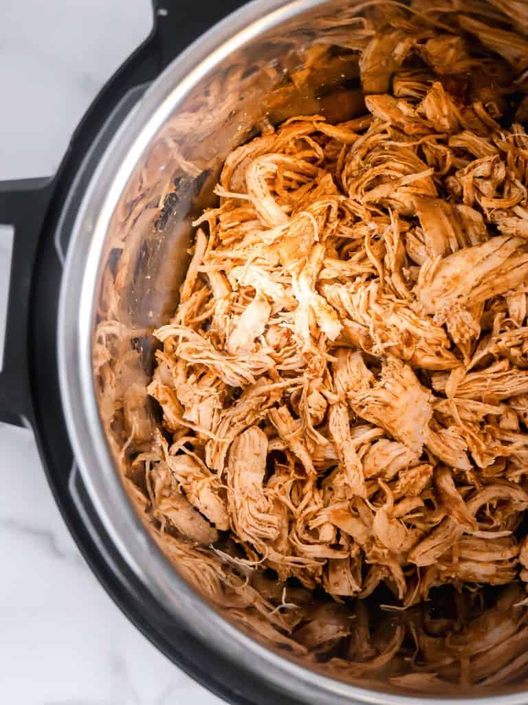 overhead half shot of shredded chicken inside instant pot pressure cooker