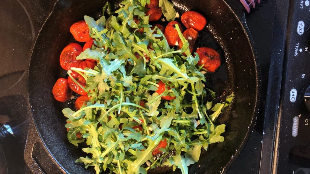 blistered tomatoes, arugula, garlic in cast iron skillet