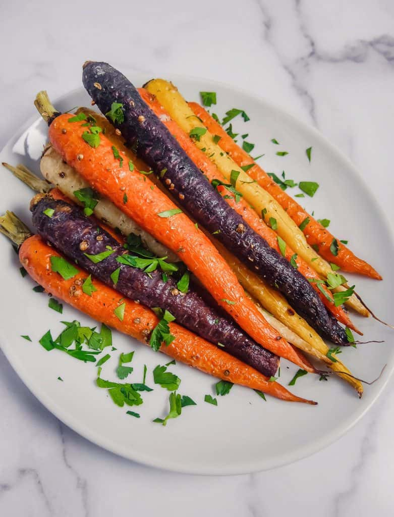 rainbow colored carrots with coriander seeds and chopped parlsey over the top stacked up on a white plate