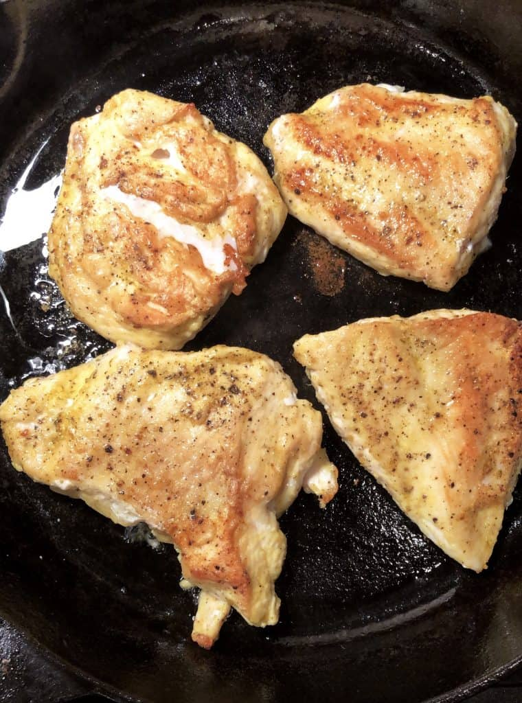 chicken breast browning in cast iron skillet