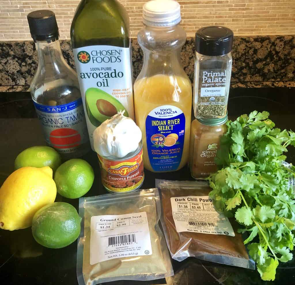 photo of ingredients for carne asada marinade. Whole lemon, limes, ground cumin, dark chili powder, bunch of fresh cilantro, orange juice, garlic head, tamari bottle, avocado oil and spices
