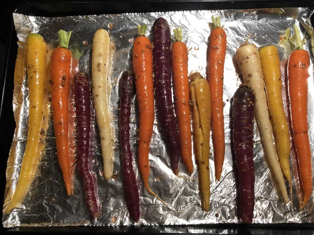 overhead shot of rainbow carrots on a baking sheet lined with aluminum foil and coriander oil brushed over the top