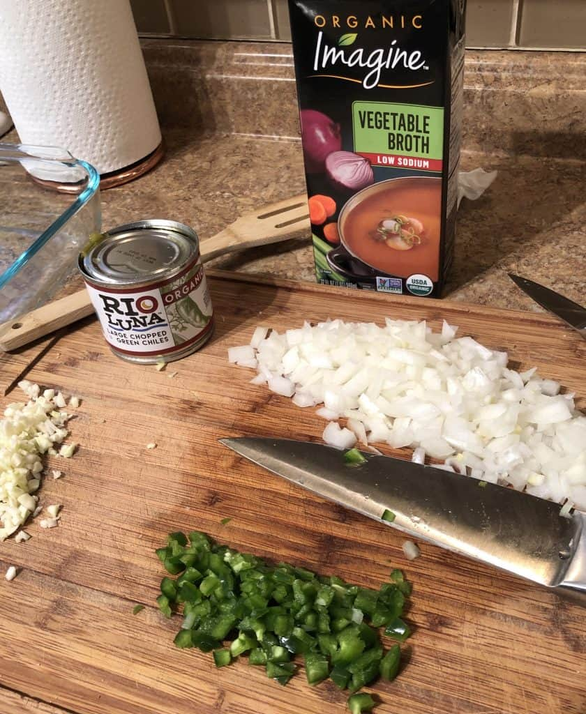 vegetable broth, hatch chilis, diced onion, garlic, and jalapeño on a cutting board