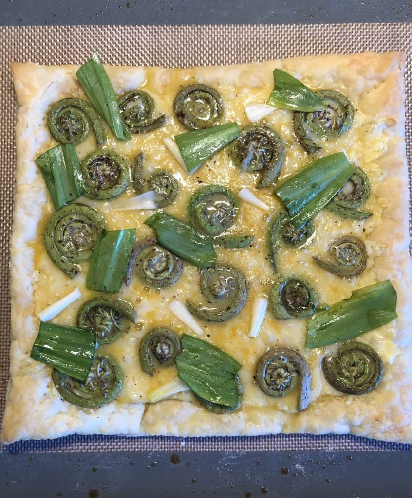 overhead shot of fiddlehead ferns and ramps spread over the puff pastry and cheese on a baking sheet