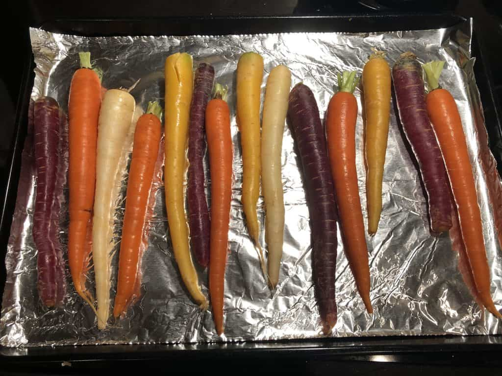 rainbow carrots tops removed, lying on a baking sheet lined with aluminum foil