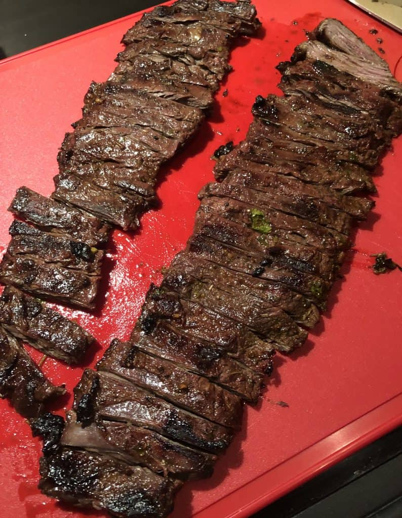 over head shot of grilled skirt steak sliced against the grain on a cutting board