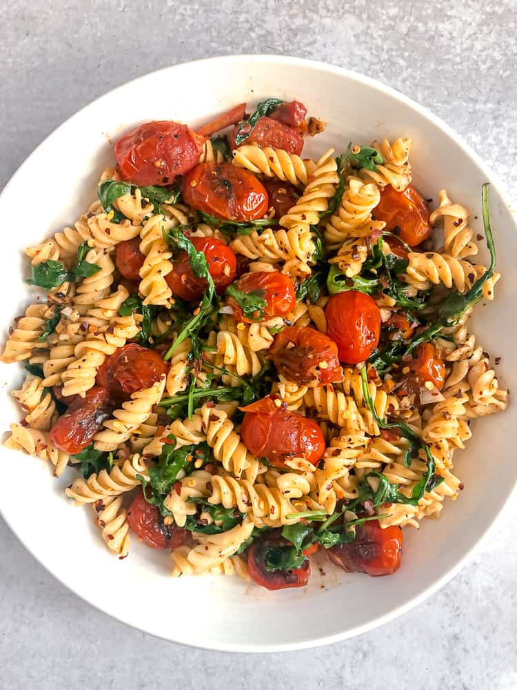 overhead photo of bowl of pasta with blistered tomatoes, pasta, and arugula