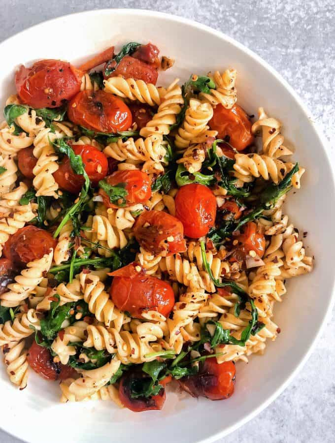 Blistered tomatoes, arugula, garlic, gluten free pasta in a bowl