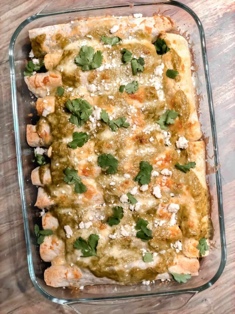 salsa verde enchiladas with melted cheese in a baking dish with cilantro