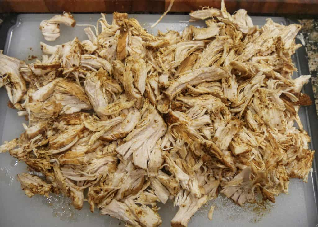 cooked shredded chicken on a cutting board