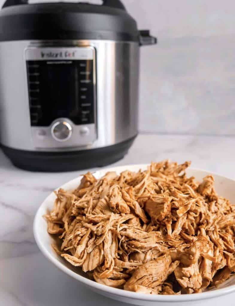 Front shot of cooked shredded chicken in a white bowl with an instant pot in the background