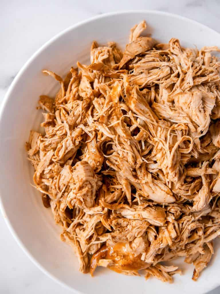 overhead shot of shredded pressure cooked chicken in a white bowl
