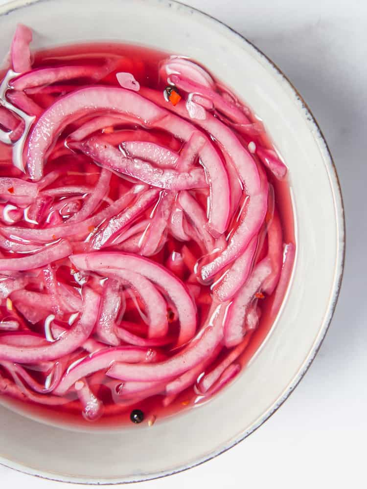 white bowl with pickled red onions inside