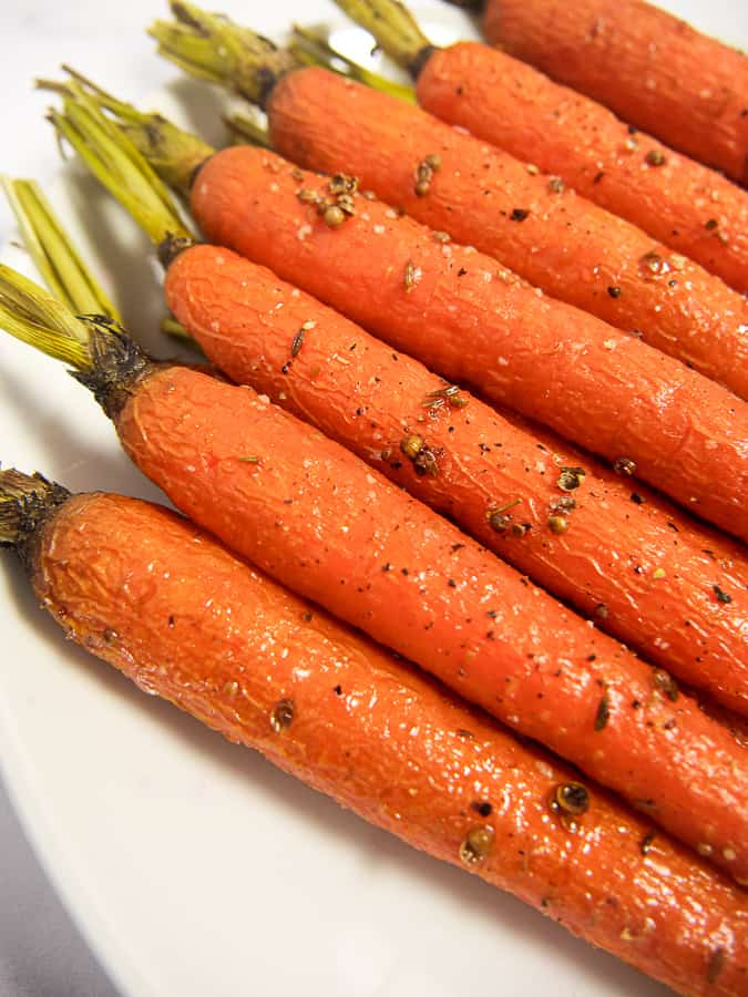 close up of honey roasted carrots with coriander seeds on a white plate