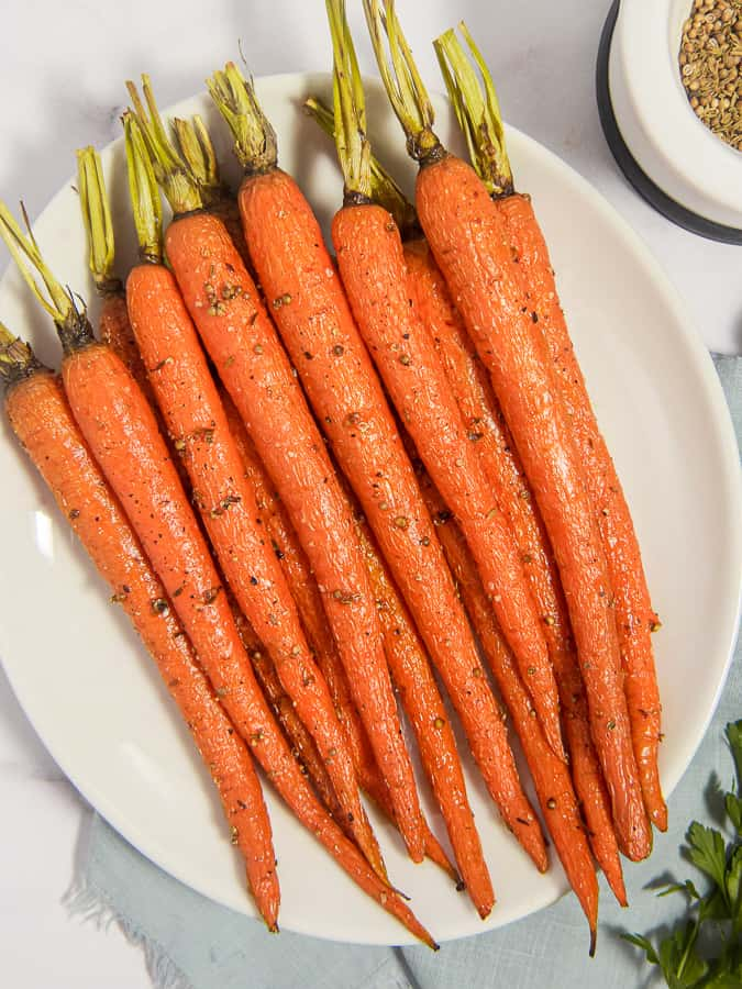 overhead photo of roasted carrots on a plate with herbs and seeds in a motar and pestle