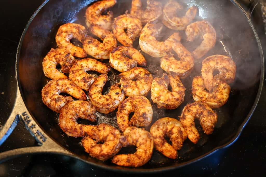 shrimp being cooked in a cast iron skillet