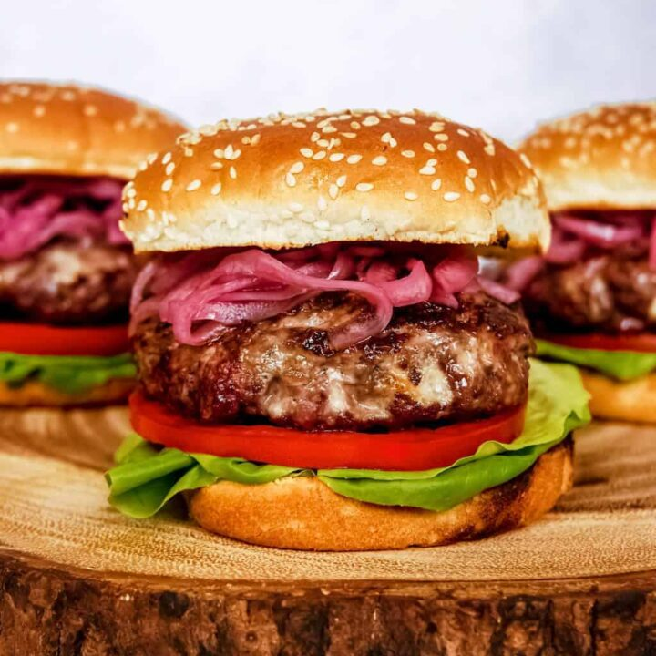 blue cheese burger with pickled red onion, lettuce, tomato, sesame seed buns, stacked on wood block