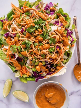 asian salad in a bowl with spicy peanut dressing and two limes