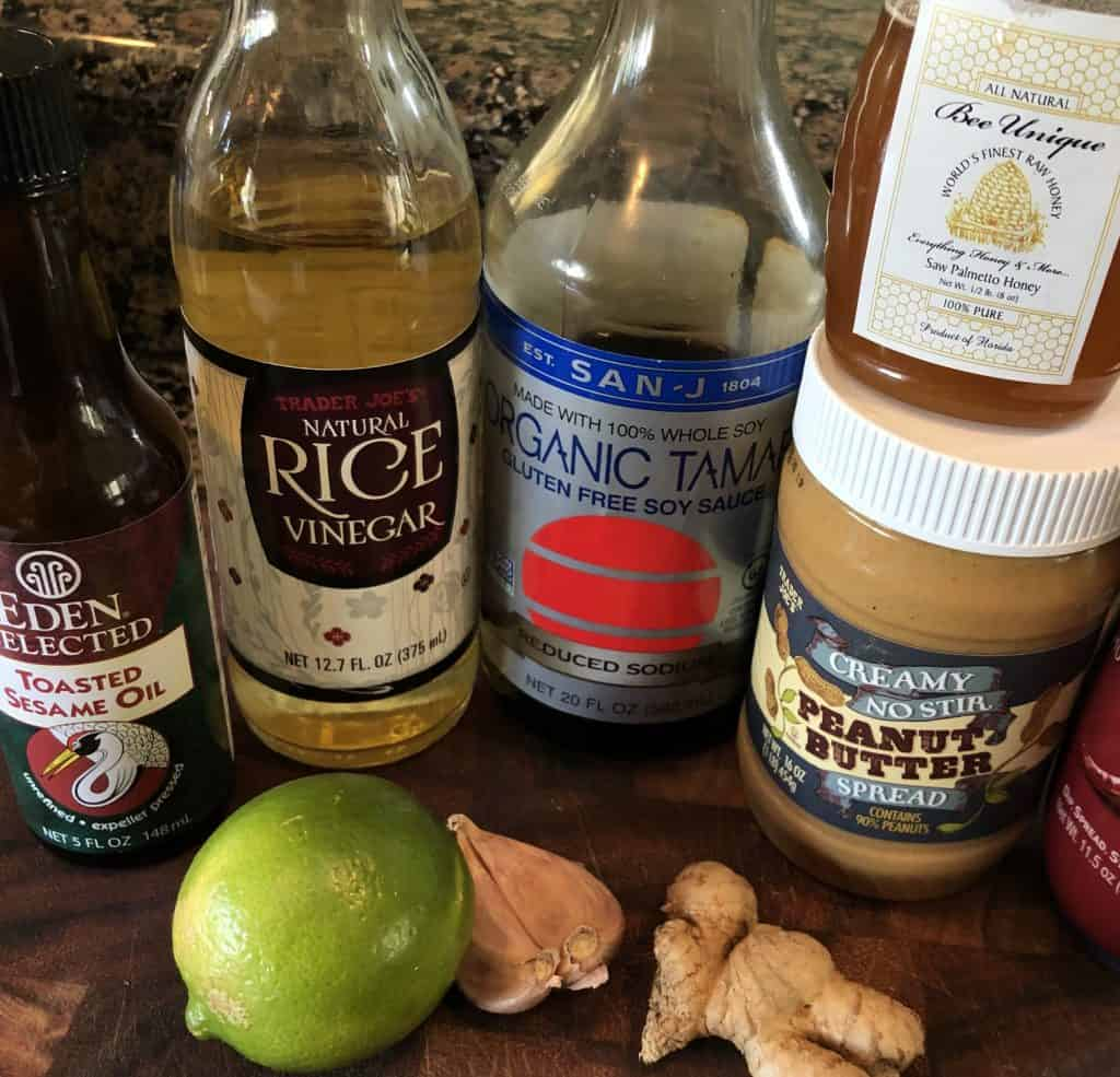 spicy peanut dressing ingredients photo of toasted sesame oil, rice vinegar, tamari, peanut butter, honey, a whole lime, two cloves garlic, knob of ginger