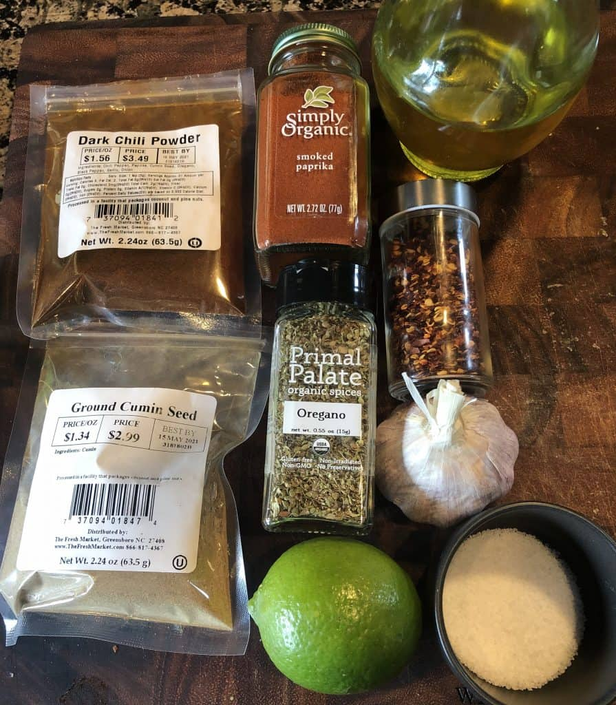 photo of ingredients used in shrimp marinade, smoked paprika, dark chili powder, ground cumin, whole lime, oregano, red pepper flakes, garlic head, olive oil, and kosher salt bowl