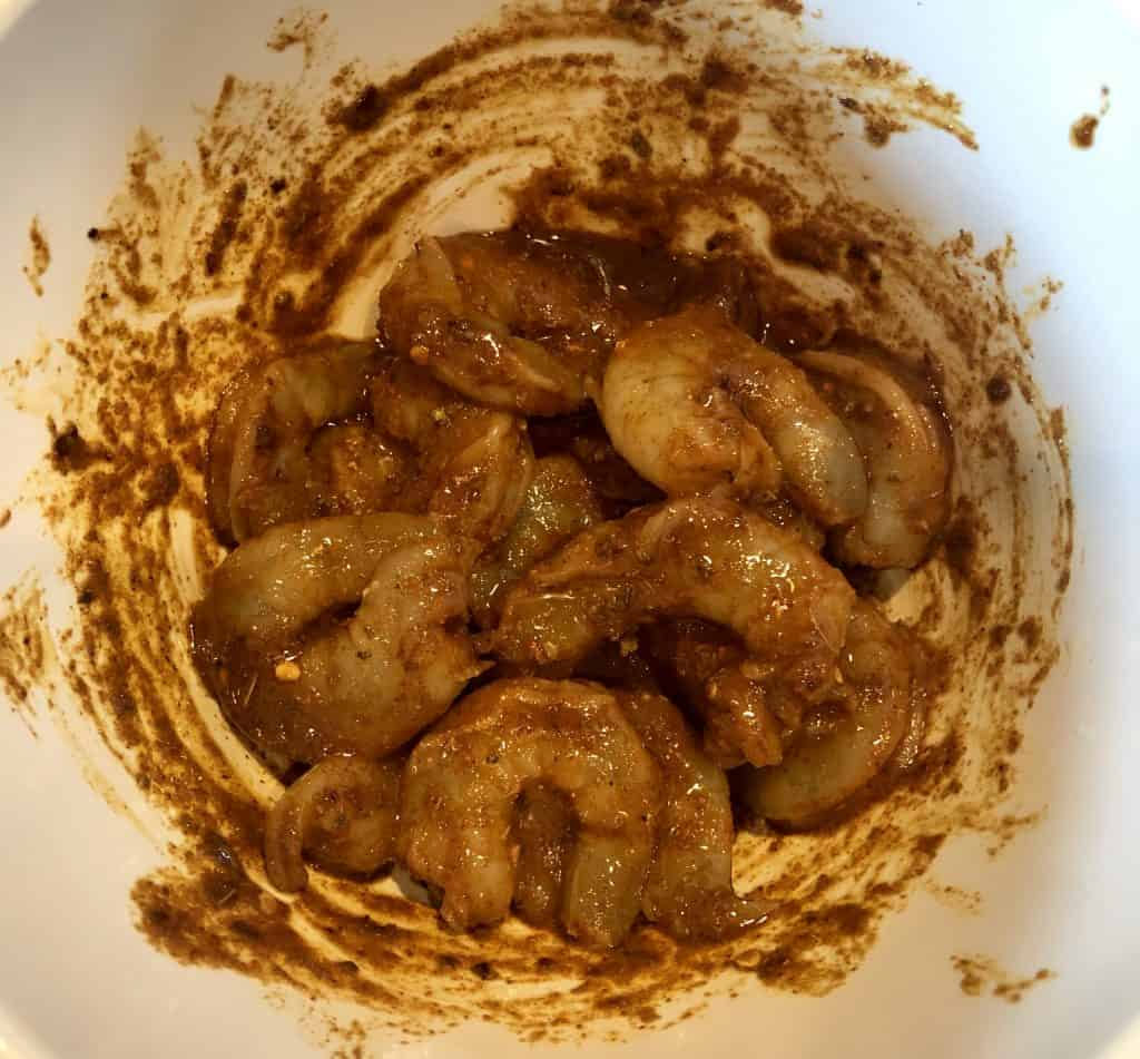 bowl of uncooked spicy shrimp, mixed in the marinade