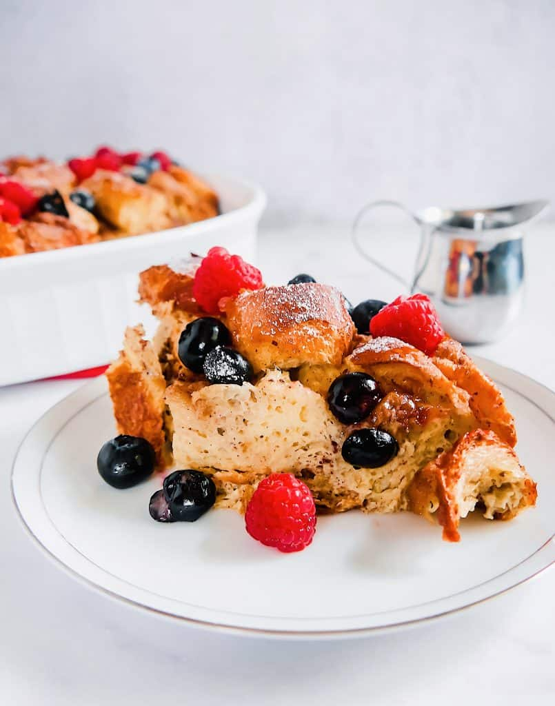 slice of french toast bake with blueberries and raspberries and maple syrup in the background