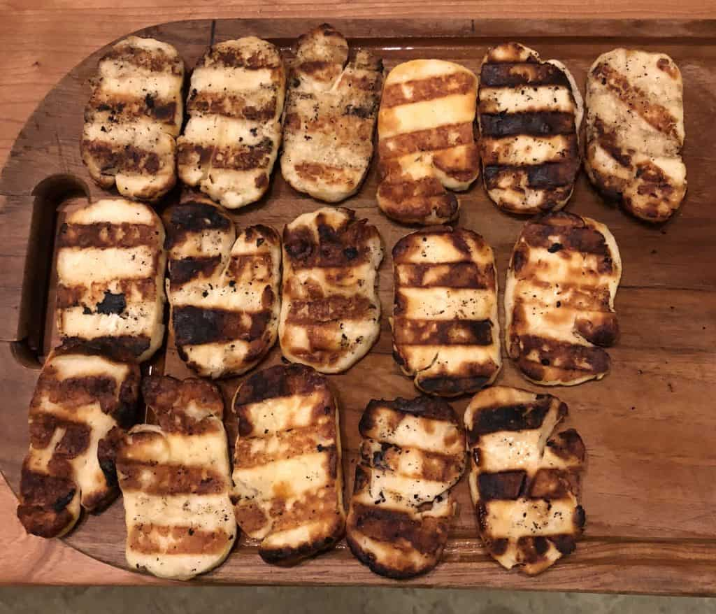 overhead shot of grilled halloumi cheese with grill marks on a wooden cutting board