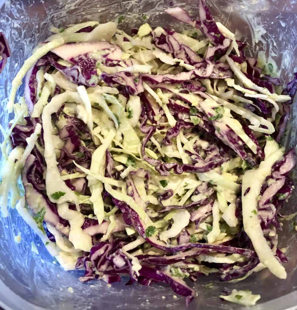 purple and green shredded cabbage in a bowl mixed with avocado crema