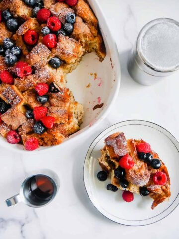 french toast casserole with berries and maple syrup and powdered sugar