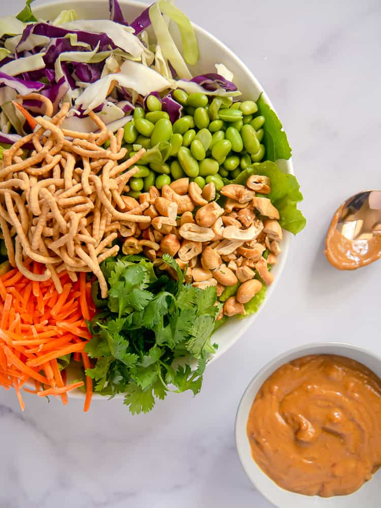 bowl with sectioned edamame, cabbage, carrots, peanuts, and peanut dressing on the side