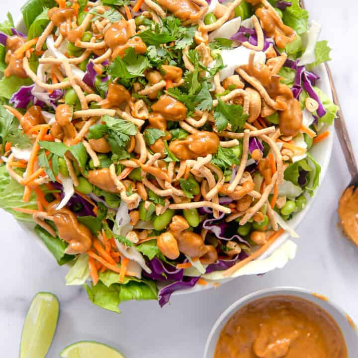 overhead photo of asian salad in a bowl with spicy peanut dressing on the side and sliced limes