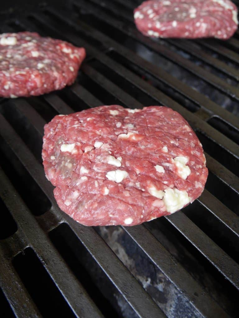 formed blue cheese burger patty on a propane grill uncooked