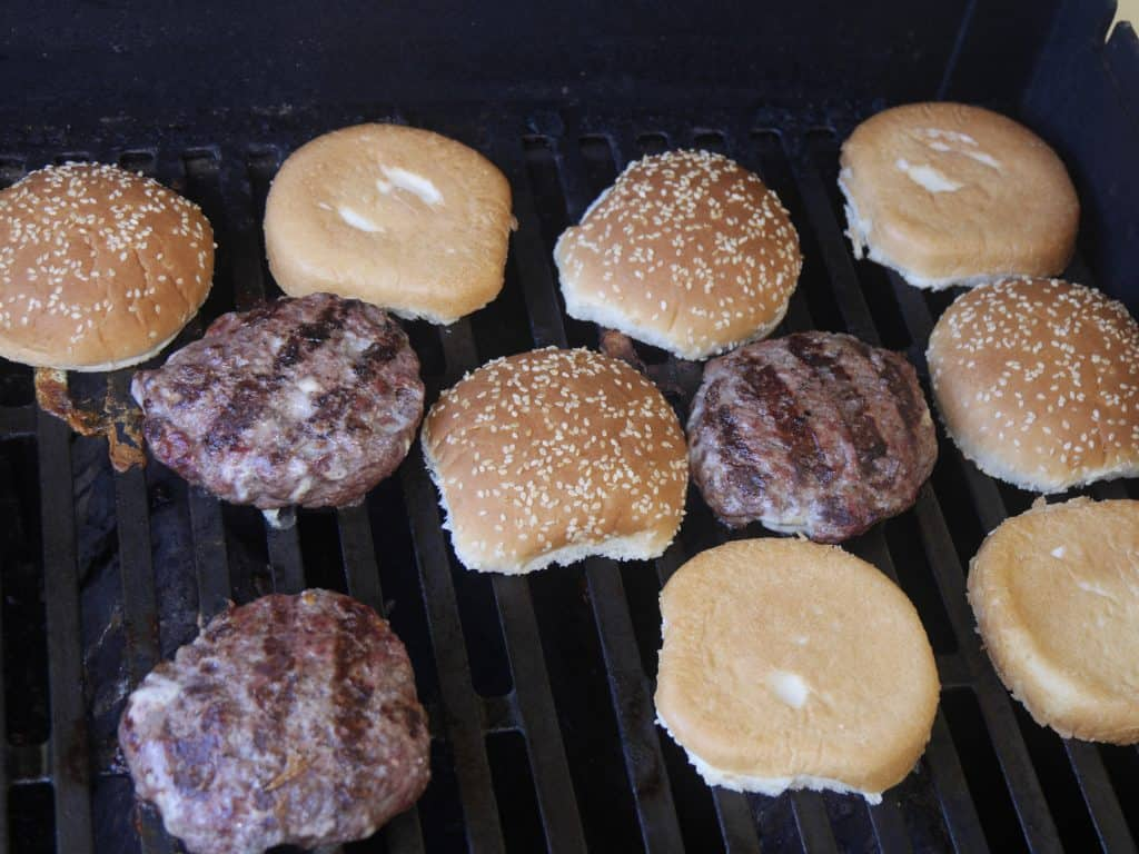 blue cheese burger patties charred on gas grill with sesame buns on grill