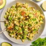 bowl with grilled corn, avocado, halloumi cheese, limes and herbs