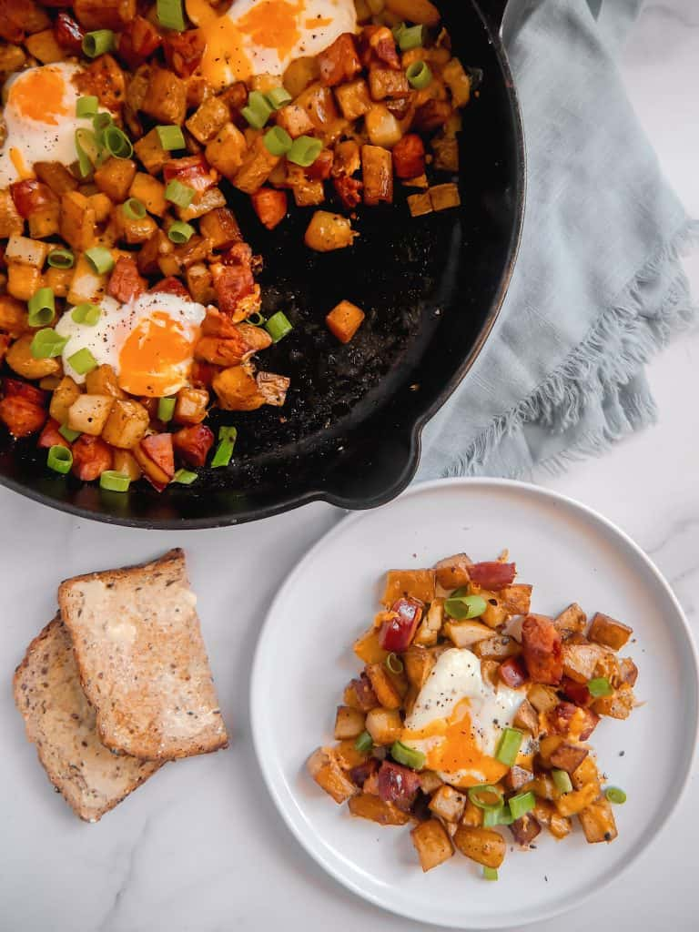overhead shot ofwhite plate with breakfast potatoes, chorizo, runny egg, with cast iron skillet in background, and buttered toast and blue napkin