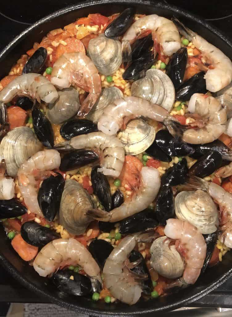 uncooked seafood being added on top of the paella rice in the skillet