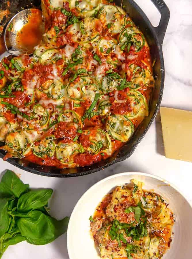 cast iron skillet with rolled cheesy zuchini and red sauce with a bowl of stuffed zucchini rolls and fresh basil