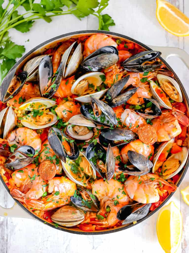 skillet full of seafood paella with herbs and lemons surrounding