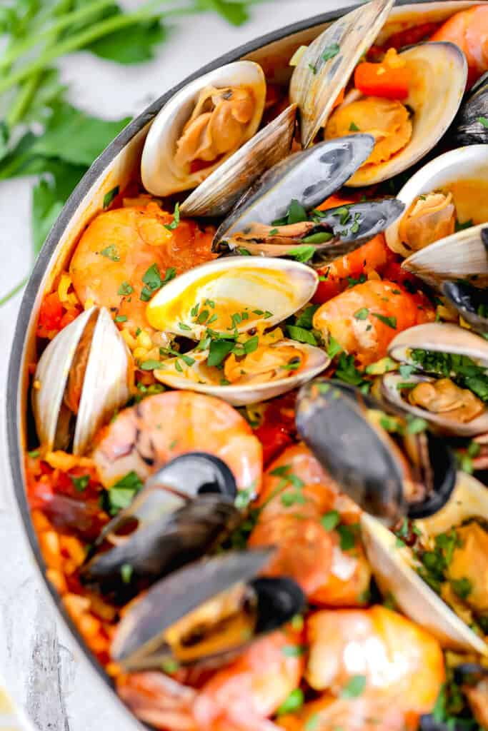 close up of clams in seafood paella in a skillet